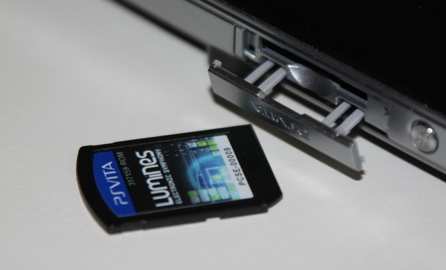 the Vita's flimsy-feeling game card slot protector, with a game card.