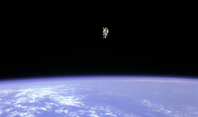 Astronaut Bruce McCandless II flying hundreds of meters from Challenger with the MMU