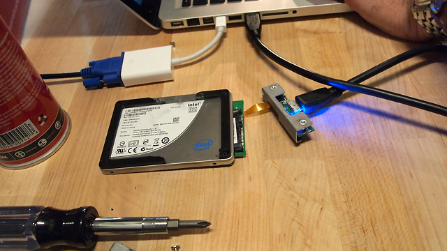 The SSD is once again attached to an SATA-to-USB adapter. You can see that some of the shock protection material has been torn off from being shot with an M-16.
