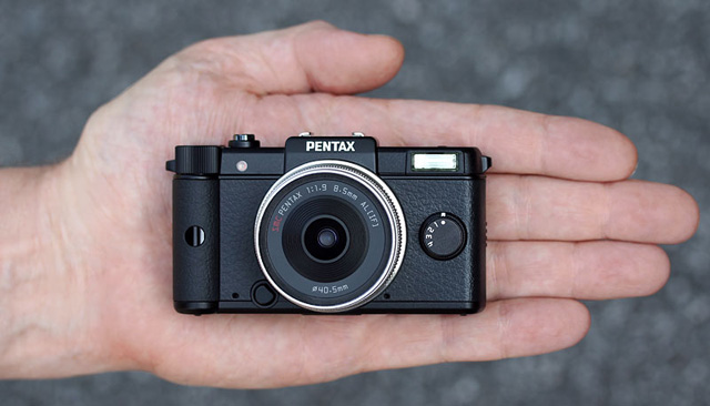 The Pentax Q's small size compared to a human hand.