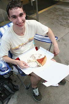Andy Pichotta enjoys some famous Giordano's Chicago-style deep dish pizza while preparing to wait over 19 hours to buy an iPhone 3G.