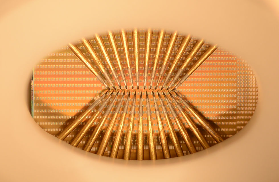A photo of a wafer full of phase-change devices (the silver squares). The probe needles are required to make the actual thing work: this is a prototype chip without the usual traces/pins that would connect it to a circuit board.