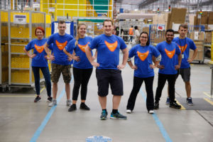 A hyper-camp photo of some Amazon warehouse workers, who have prepared for Prime Day by donning a special t-shirt and probably doing some lunges while watching a Mr. Motivator VHS.