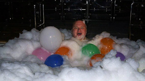 Kim Dotcom enjoys a bath with balloons.