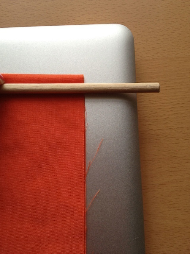 The dowel should overhang the edge of the fabric by a bit. How far is a stylistic choice, but you need some space for the shoelace knots.