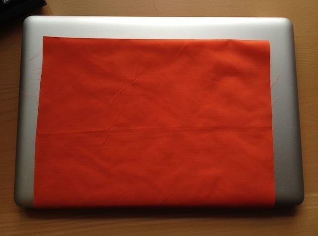 The laptop hammock fabric, cut to size, falling an inch or two short of the edge of the computer on three sides.